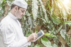 Homem de negócios muçulmano árabe que trabalha no tablet pc fotos de stock royalty free