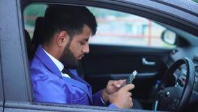 Homem de negócios muçulmano que senta-se no carro e que datilografa no smartphone video estoque