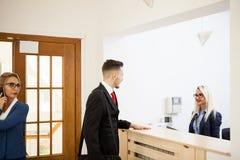Homem de negócios na área de recepção do escritório que fala com secretário imagens de stock
