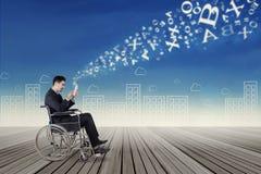 Homem de negócios na cadeira de rodas que envia a informação Fotografia de Stock