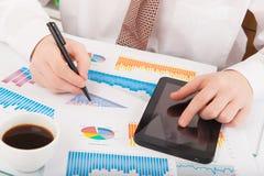 Homem de negócios que analisa gráficos e cartas Imagem de Stock Royalty Free
