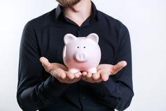 Homem de neg?cios na camisa preta que guarda um mealheiro Dinheiro da economia imagem de stock royalty free