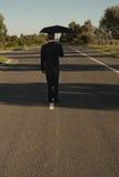 Homem de negócios na estrada com guarda-chuva Imagens de Stock Royalty Free