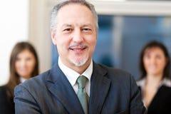 Homem de negócios na frente de sua equipe Fotografia de Stock Royalty Free