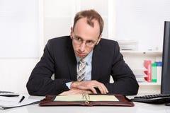 Homem de negócios na mesa com problemas, esforço e assento sobrecarregado fotografia de stock