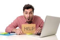 Homem de negócios na mesa de escritório que trabalha no portátil do computador que pede a ajuda que guarda o sinal do cartão que  Imagem de Stock Royalty Free