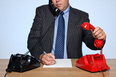 Homem de negócios na mesa que responde a dois telefones. Fotos de Stock Royalty Free
