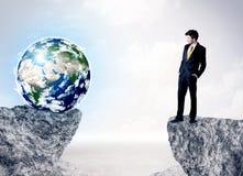 Homem de negócios na montanha da rocha com um globo Imagem de Stock