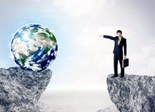 Homem de negócios na montanha da rocha com um globo Foto de Stock