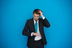 Homem de negócios na precipitação que olha seu relógio, correndo tarde Foto de Stock Royalty Free