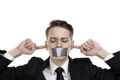 Homem de negócios na série com olhos fechados, orelhas e fita sobre sua boca foto de stock