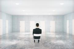 Homem de negócios na sala com muitas portas Fotos de Stock