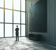 Homem de negócios na sala do sótão com imagem grande preta vazia, s de couro Imagens de Stock
