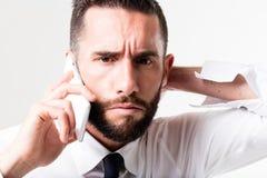Homem de negócios na sua discussão móvel Imagens de Stock Royalty Free