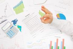 Homem de negócios na tabela com os dados financeiros diferentes que mostram o sinal - APROVADO Imagens de Stock