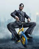 Homem de negócios Nerdy que monta uma bicicleta pequena imagens de stock