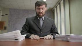 Homem de negócios nervosamente que assina e que carimba originais entrantes o trabalhador de escritório desloca papéis de uma pil vídeos de arquivo