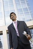Homem de negócios With Newspaper Standing em Front Of Building Fotos de Stock