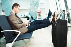 Homem de negócios no aeroporto com smartphone e mala de viagem Fotos de Stock Royalty Free