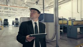 Homem de negócios no capacete de segurança que anda através da fábrica video estoque