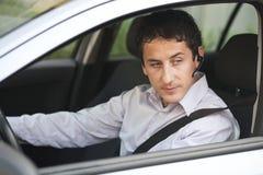 Homem de negócios no carro com bluetooth imagem de stock