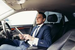 Homem de negócios no carro com a tabuleta fotos de stock royalty free