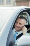 Homem de negócios no carro que fala no telefone móvel fotografia de stock