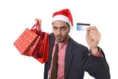 Homem de negócios no chapéu de Santa Claus Christmas que guarda sacos ensopados e cartão de crédito no preocupado e esforço Fotografia de Stock Royalty Free