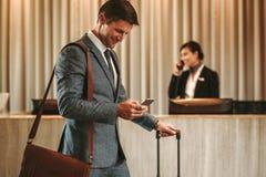 Homem de negócios no corredor do hotel com telefone celular e bagagem fotos de stock royalty free