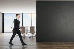 Homem de negócios no escritório com parede preta fotos de stock royalty free
