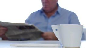 Homem de negócios no escritório em uma pausa do café que relaxa lendo um jornal video estoque