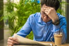 Homem de negócios no escritório, lendo notícias de última hora más em um jornal financeiro, é chocado e de ajuste seus vidros Fotos de Stock
