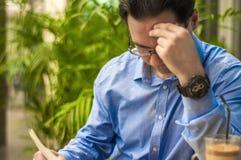 Homem de negócios no escritório, lendo notícias de última hora más em um jornal financeiro, é chocado e de ajuste seus vidros Imagem de Stock