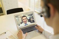 Homem de negócios no escritório na videoconferência com auriculares, Skype Fotografia de Stock
