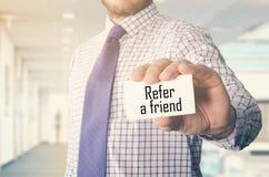 homem de negócios no escritório que mostra o cartão com texto: Consulte um amigo imagens de stock royalty free