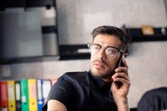 Homem de negócios no escritório que responde ao telefone imagens de stock royalty free