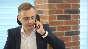 Homem de negócios no espaço de funcionamento usando o telefone vídeos de arquivo