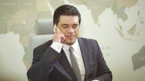 Homem de negócios no espaço de funcionamento usando o telefone video estoque
