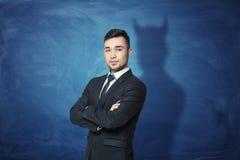 Homem de negócios no fundo azul do quadro com sua sombra que tem chifres do diabo imagem de stock royalty free