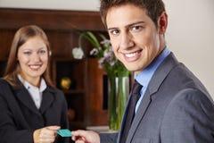 Homem de negócios no hotel que obtém o cartão chave Fotografia de Stock