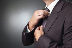 Homem de negócios no laço preto do traje sua gravata foto de stock royalty free