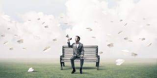 Homem de negócios no parque do verão que anuncia algo no altifalante a Fotografia de Stock Royalty Free