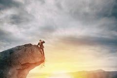 Homem de negócios no pico de uma montanha para encontrar o negócio novo foto de stock