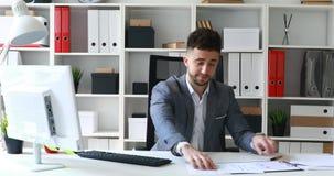 Homem de negócios no revestimento cinzento que senta-se na tabela no escritório branco e em originais de oferecimento