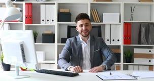 Homem de negócios no revestimento cinzento que senta-se na tabela no escritório branco e que exulta no sucesso