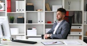 Homem de negócios no revestimento cinzento que senta-se na tabela no escritório branco, olhando o pulso de disparo e saindo na es