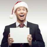 Homem de negócios no sinal da terra arrendada do chapéu de Santa Fotografia de Stock Royalty Free