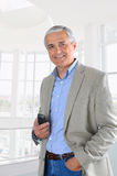 Homem de negócios no telefone de pilha hodling do ajuste do escritório Fotografia de Stock