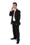 Homem de negócios no telefone, na posição e na vista à câmera foto de stock