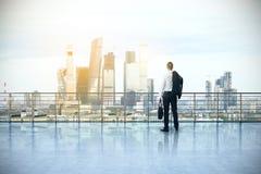 Homem de negócios no telhado que olha a cidade fotografia de stock